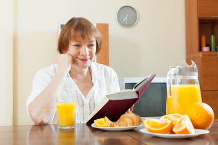 Positive senior woman having breakfast with book in morning Stock Photo - 30930568