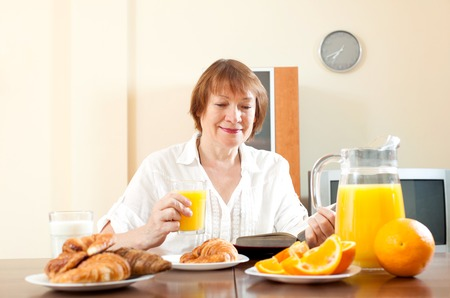 mature woman reading book during breakfast with croissants in morning at home Stock Photo - 30930569