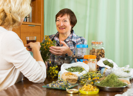 Two positive pensioner sitting at the table with herbal tea and herbs photo