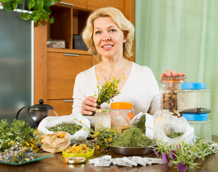 medical herbs: Smiling aged woman sitting at table with herbs in home