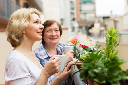 Smiling senior female pensioners relaxing with cup of coffee on balcony Stock Photo