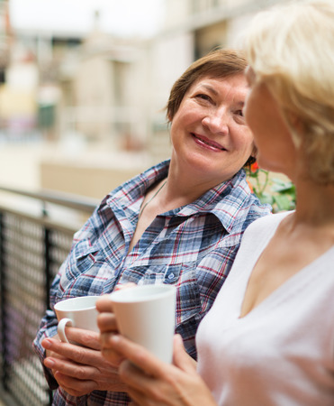 Two happy female pensioners staying on balcony with cup of tea and smiling  photo