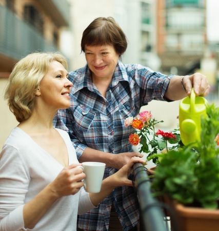 Two happy mature women drinking tea on balcony and smiling photo