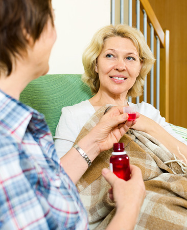 linctus: Professional retirement home employee offering  mixture to smiling patient