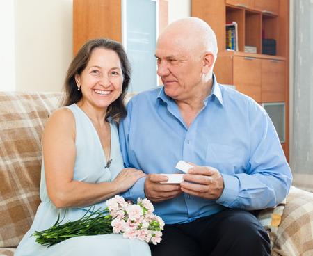 Senior man presenting smiling mature woman jewel in box  at home    photo