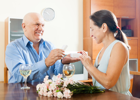elderly man with mature woman having romantic date at home photo