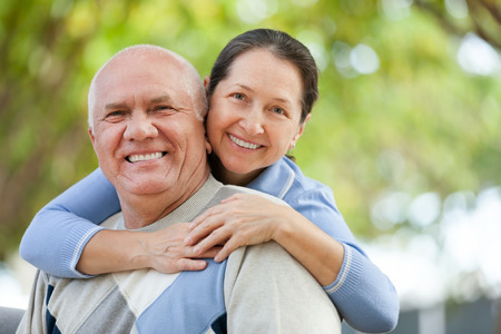 family fall: Portrait of smiling mature couple in sweaters at autumn park