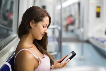 train: Woman using ereader in subway train at metro Stock Photo