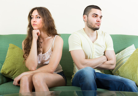 Young married couple sitting sad on sofa after quarrel at home  photo