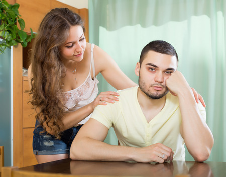 fracas: Loving woman asking for forgiveness from man after quarrel at home Stock Photo