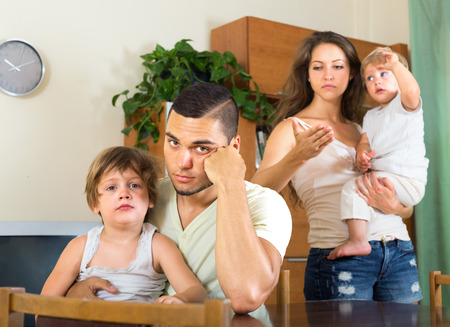 man and woman with two children quarreling at home photo