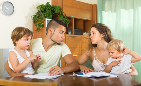 Married couple having quarrel in front of children at home photo