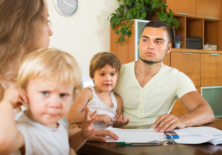 Young parents with little children having conflict in home interior  photo