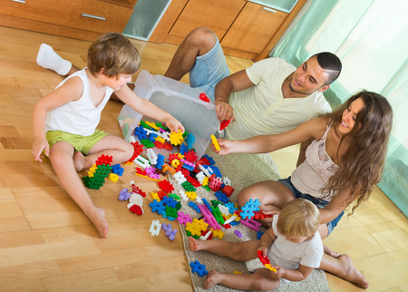 Ordinary happy family of four relaxing at home with toys  photo