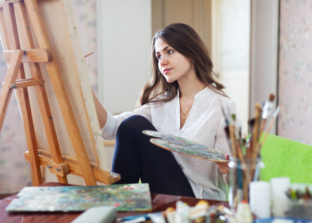 easel: Long-haired female artist paints picture on canvas with oil paints