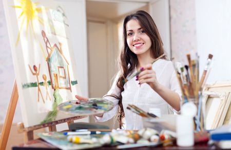 Young woman paints home of dreams on canva photo