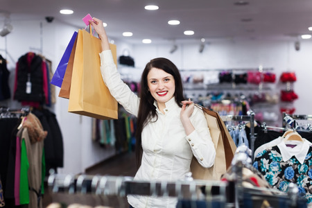 Smiling girl with shopping bags at clothing store photo