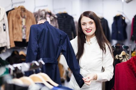 ordinary woman: Ordinary woman choosing jacket at clothing boutique Stock Photo
