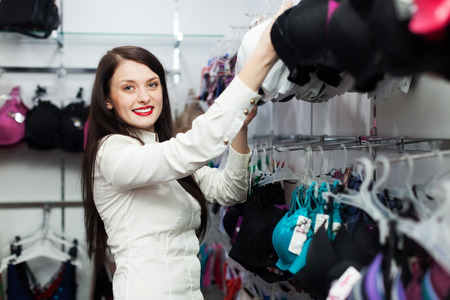 clothing store: Smiling woman choosing underwear at clothing store