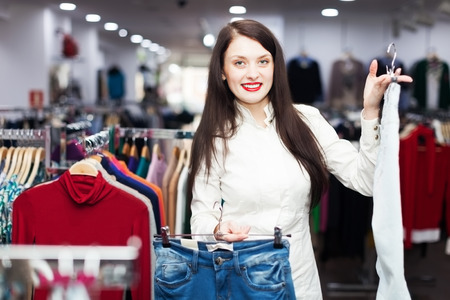 hellion: Girl choosing trousers at clothing boutique Stock Photo
