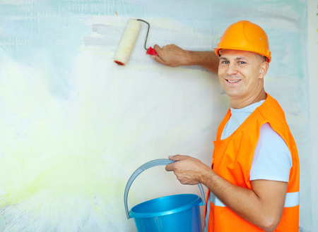unskilled worker: male house painters with paint rollers in new house