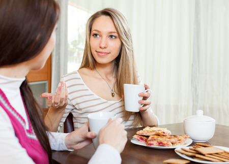 blabber: two young women sitting at table, gossiping and drinking tea Stock Photo