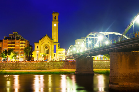 ebre: Night view of Bridge called Pont de lEstat over Ebro river and church in Tortosa, Spain Stock Photo