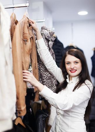tienda de ropa: Mujer ordinaria elegir chaqueta en una tienda de ropa