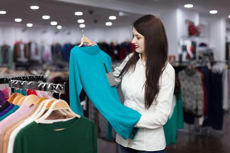 ordinary woman: Ordinary woman choosing sweater at clothing shop