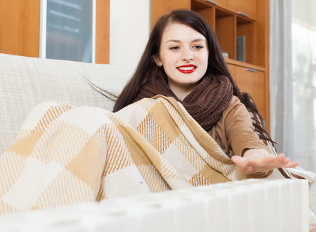 long-haired woman warming near electric heater at  home