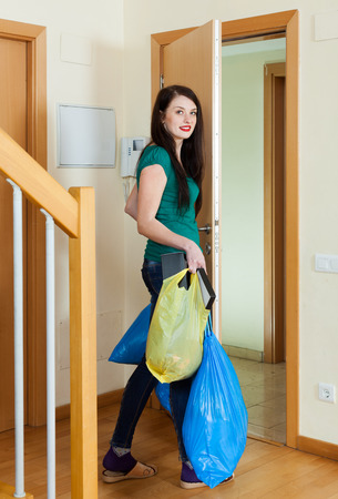 put away: Brunette woman taking away the garbage at home Stock Photo