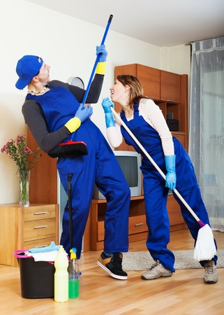 impish: Playful housecleaners cleaning at house Stock Photo