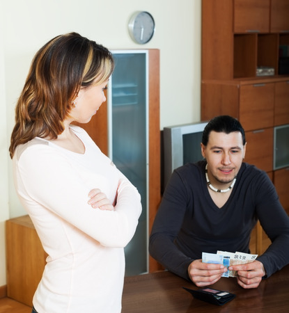covetous: Financial problems in family. Man counting cash, woman watching him in home