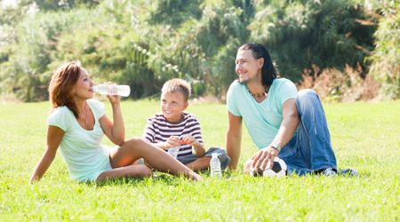 Smiling family enjoying time  in sunny park photo