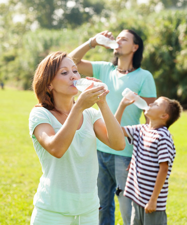 ordinary family of three drinking water from  bottles photo