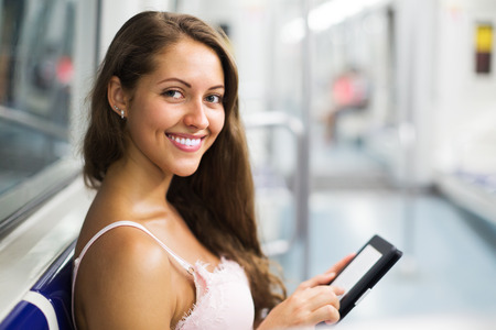 ereader: Smiling young woman using ereader in subway train at metro  Stock Photo