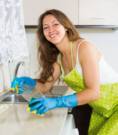 Smiling housewife in apron cleaning furniture in kitchen  photo