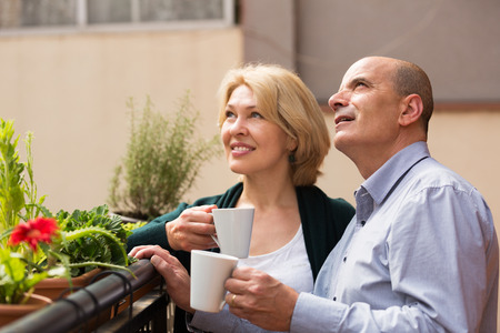 Smiling couple of pensioners drinking tea and chatting on balcony  photo