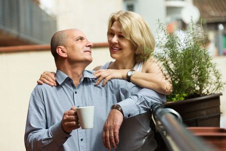 Happy senior couple discussing and drinking coffee at balcony photo