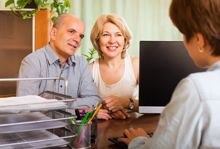Positive senior couple opening saving account in bank