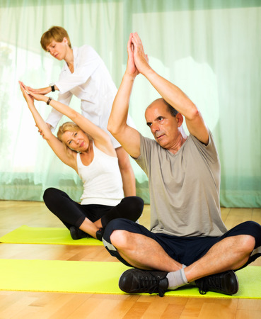 Female yoga instructor showing new asana elderly couple  photo