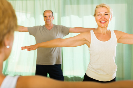 incline: Female trainer showing happy senior couple how to incline the body