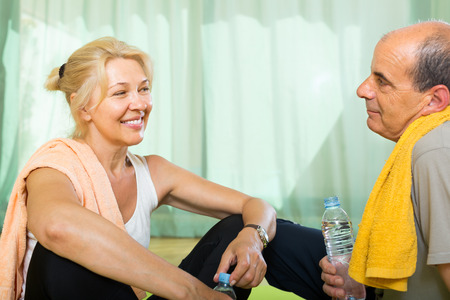 staying: Active elderly spouses with bottles of water after morning exercises. Focus on woman
