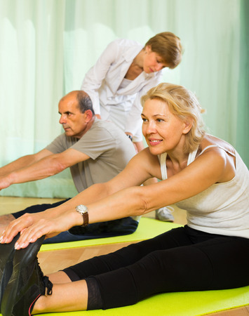spouses: Medical staff at gym helping mature spouses to take correct position. Focus on woman  Stock Photo