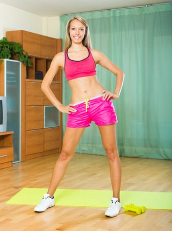 perspire: Smiling happy girl working out on exercise mat in the living room Stock Photo