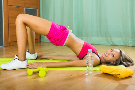 house trained: Attractive sporty girl working out on exercise mat in the living room  Stock Photo