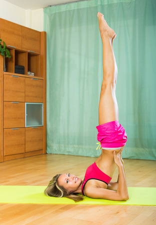 house trained: Cheerful girl standing in yoga position on exercise mat at home