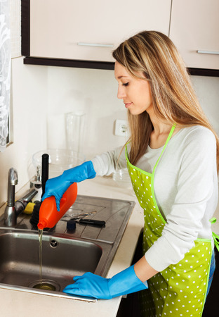 woman cleaning pipe with detergent in kitchen  photo