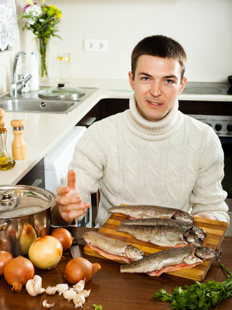 brook trout: Smiling man with salmon fish  in home kitchen