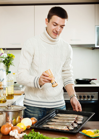 brook trout: Handsome man adding spices in raw fish on roasting pan Stock Photo